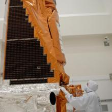 A Technician Inspects the Spacecraft During a Media Event at Astrotech's Facility