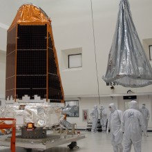 A Protective Cover is Lifted Toward the Spacecraft Prior to Transport to the Hazardous Processing Facility