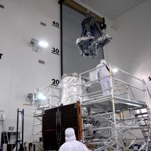 An Environmental Covering Being Lowered Toward the Spacecraft