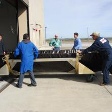Workers Move the Payload Fairing into Astrotech's Facility