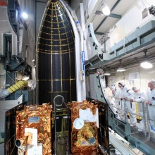 A Section of the Delta Payload Fairing Moves into Place Around the Spacecraft