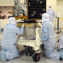 Workers and Technicians Position OCO-2 onto the Test Fixture
