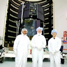 Astrotech Team Members Stand in Front of the RBSP Twin Satellites Prior to Encapsulation